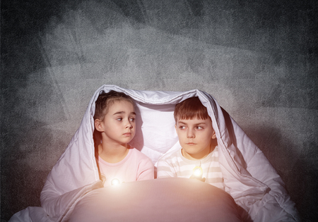 Scared children with flashlights lying in bed. Little sister and brother hiding under blanket together. Covered kids afraid of dark at night on background of grey wall. Night terrors of child.