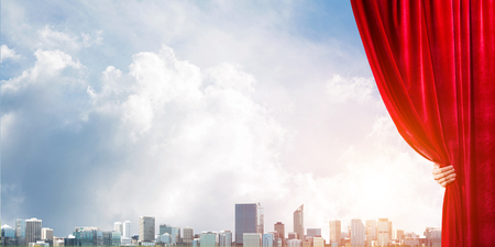 Human hand opens red velvet curtain to modern cityscape and cloudy sky Stockfoto