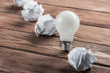 Incandescent bulb and crumpled white paper balls on brown wooden table