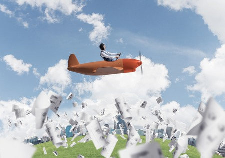 Businessman in leather helmet and goggles flying in propeller plane. Aviator driving small airplane above falling paper sheets with business infographics. Rounded city skyline with high skyscrapers Imagens - 122746213