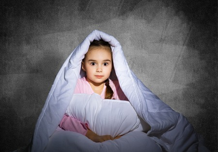 Frightened girl hiding under blanket. Scared kid lying in his bed at home. Fear of the dark. Beautiful little girl can not sleep at night. Portrait of child in pajamas on background of grey wall. Stockfoto