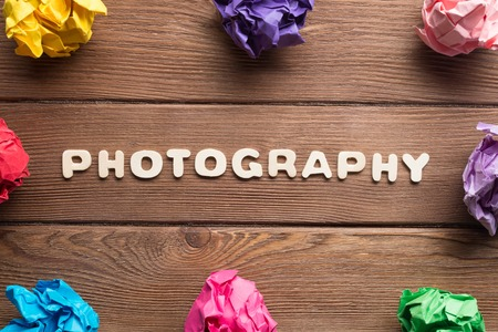 Set of multiple colorful crampled paper ball placed in circle on wooden table Stockfoto
