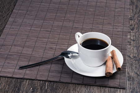 Cup of black coffee on wooden table with bamboo mat. Cinnamon sticks on white porcelain saucer with spoon. Close up natural aromatic hot drink in restaurant. Morning coffee break. Stockfoto