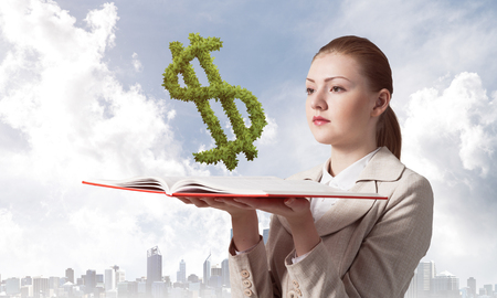 Businesswoman with green plant shaped dollar sign above opened notebook. Banking and investment services. Elegant young woman in white business suit on background of cityscape and blue sky.