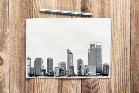 Big city skyline pencil draw on textured wooden background. Panorama of modern downtown with high office buildings sketch on wooden surface. Commercial real estate architecture and construction.