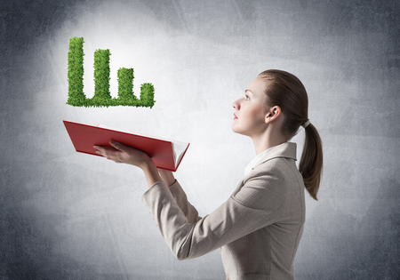Businesswoman showing green plant in shape of growth financial graph above opened notebook. Business presentation and report. Elegant young woman in white business suit on background of grey wall.