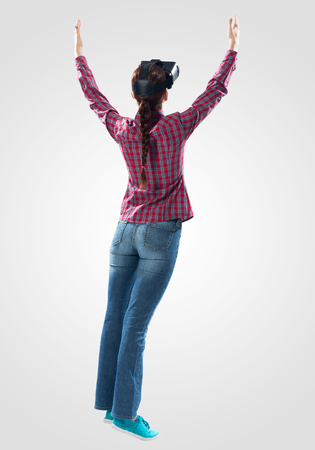 Young woman wearing virtual reality glasses against gray background. Beautiful woman in checkered shirt and jeans with hands up. Interacting with digital interface. Future technology concept Stockfoto