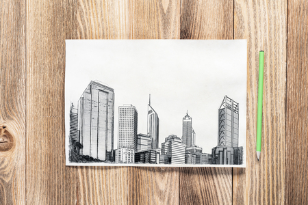Modern city center pencil draw. Urban architecture hand drawn sketch on wooden table. Sheet of paper on textured natural wooden background. Architecture agency template. View from above with copyspace Stockfoto