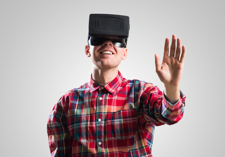 Young man in checked shirt wearing virtual helmet against gray background