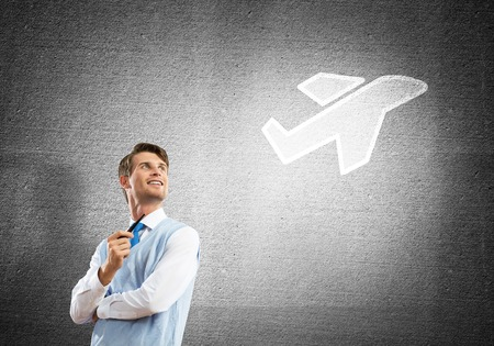 Confident and young businessman smoking pipe and drawn airplane on gray wall background