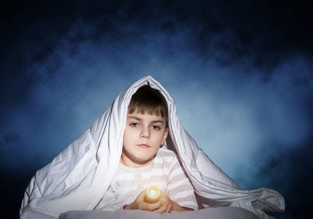 Serious child with flashlight hiding under blanket. Attentive kid lying in his bed at home. Fear to sleep in darkness at night. Portrait of little boy in pajamas on background of deep starry sky.