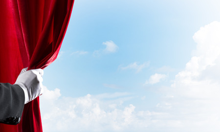 Human hand in glove opens red velvet curtain on blue sky background Stockfoto