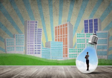 Businesswoman inside light bulb against city drawn concept Stockfoto
