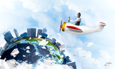 Man in aviator hat with goggles driving propeller plane. Earth globe with high modern buildings. Funny man having fun in small airplane. Blue cloudy sky with flying hot air balloons and paper planes