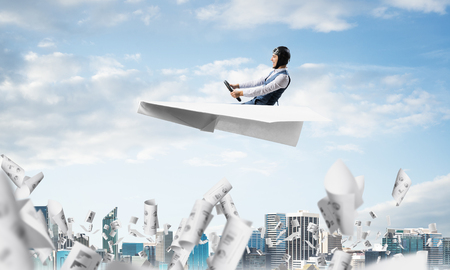 Businessman driving paper plane above business center in cloudy blue sky. Papers falling down on background of skyscrapers. Pilot in leather helmet sitting in paper plane. Risk management concept