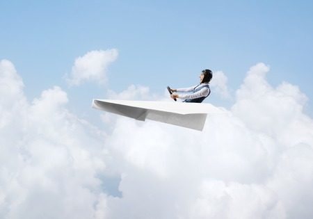 Aviator having fun in aircraft. Pilot in leather helmet and goggles driving paper plane in cloudy blue sky. Funny man flying in small paper airplane. Cloudscape background with fluffy clouds.