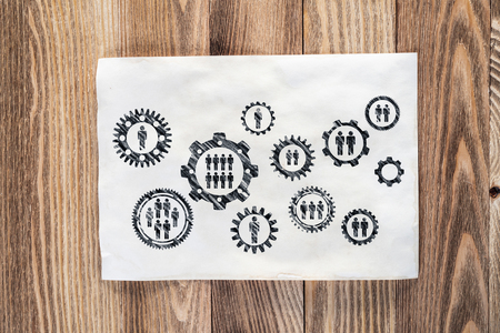 Business process management pencil hand drawn with group of rotating cogwheels. Human resources sketch on wooden desk. Workplace with sheet of paper on wooden desk. Social communication infographics Stock Photo