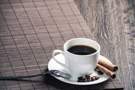 Cup of espresso coffee on wooden table with bamboo mat. Coffee beans and cinnamon sticks on white porcelain saucer. Close up natural aromatic hot drink in restaurant. Morning coffee break. Stock Photo