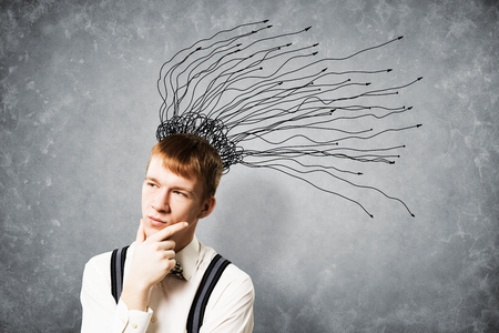 Thoughtful redhead student brainstorming. Young scientist thinking about something. Creativity and problem solving. Clever boy on background of grey wall with many arrows as hair sketch overhead. Imagens - 122874437