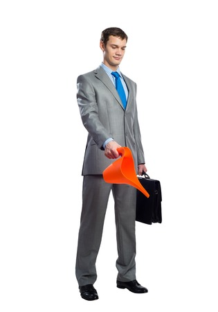 Businessman wears grey suit and blue tie with black leather suitcase holding orange plastic watering can. Portrait of young caucasian man on white background. Side view corporate businessperson.