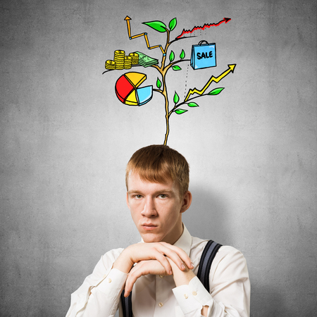 Serious student with arms touching his chin and thinking about something. Redhead boy with drawing ideas tree above head. Clever guy wears white shirt and suspenders on background of grey wall.