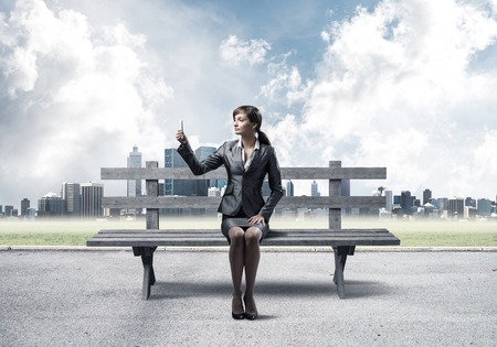 Business woman taking selfie photo or chatting with smartphone. Attractive girl using mobile phone on wooden bench. Mobile marketing and communication. Modern cityline panorama in sunny day
