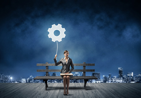 Young woman holding open book on wooden bench outdoor. Beautiful girl with gearwheel illuminated symbol in night sky. Modern cityscape panorama at night. Engineering and development concept