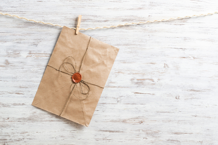 Old paper envelope hanging on rope on wooden background. Twine rope with wooden clothespins. Brown letter envelope with wax seal stamp. Retro communication and correspondence. Delivery service layout Stock Photo