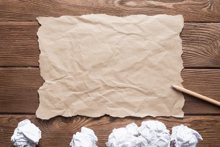 Crumpled brown paper sheet and pencil on wooden table Stock Photo - 122994647