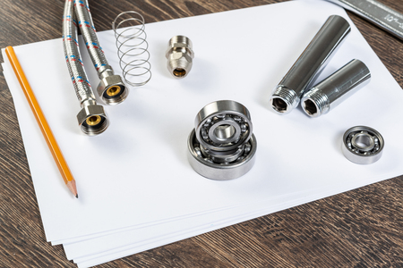 Plumbing pipeline and ball bearings laying on table. Water fittings and connections with segments of braided hose. Steel details for engine mechanisms. House infrastructure designing and installation
