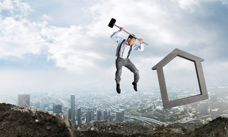 Jumping businessman crashing big house symbol with city view on background. 3D rendering. Banco de Imagens