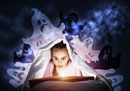 Scared little girl reading fairytales in bed. Child with book hiding under blanket. Girl in pajamas and funny ghosts back on night sky. Bedtime and magic stories reading. Light shining from open book Reklamní fotografie