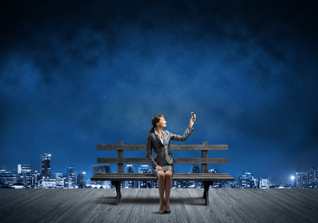 Young woman in business suit holding smartphone with raised hand. Beautiful girl with mobile phone on wooden bench. Mobile marketing and digital technology. Modern cityline panorama at night.