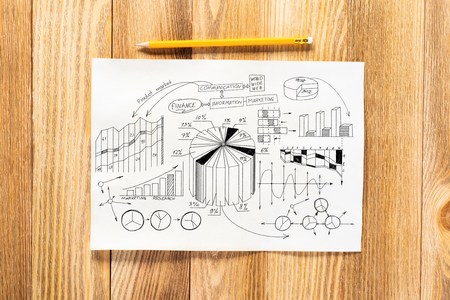 Money management and financial chart pencil hand drawn with group of business doodles. Workplace with paper and pencil lying on wooden desk. Business presentation. Finance and investment concept