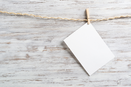 Blank sheet of white paper hanging on twine rope with wooden clothespins. Elegant photo frames on painted background. Scrapbooking and handmade creativity. Wooden wall with copyspace for text Reklamní fotografie