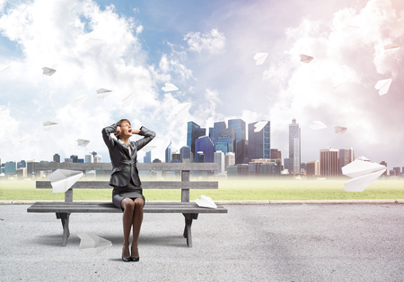 Stressful woman sitting on wooden bench. Emotional screaming girl keeps hands on head. Businesswoman in despair on background modern cityline panorama with flying paper planes. Woman call for help. Stockfoto - 123115351