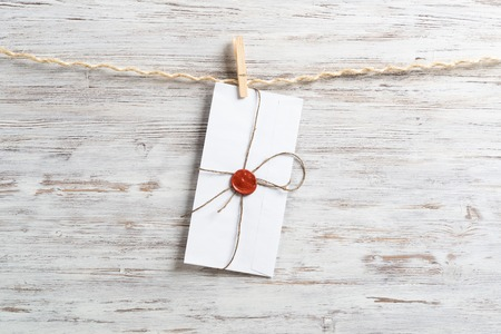 White classic envelope hanging on twine rope with clothespins. Vintage declaration of love on wooden painted background. Retro letter envelope with sealing wax stamp. Romantic wedding invitation.