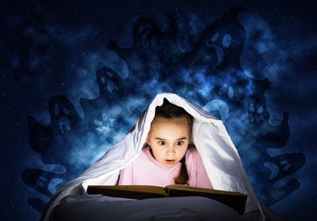 Engrossed little girl reading book in bed after bedtime. Kid in pajamas with flashlight hiding under blanket. Fearful girl and imaginary monsters on deep blue background. Child reading fairy tales. Stok Fotoğraf