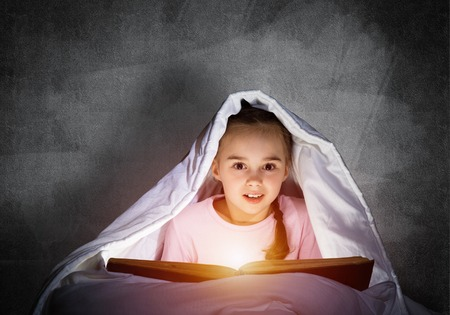 Little girl reading book in bed before going to sleep. Pretty child with flashlight hiding under blanket. Kid can not sleep at night. Portrait of beautiful girl in pajamas on background of grey wall.