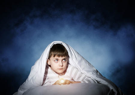 Frightened child with flashlight hiding under blanket. Scared kid lying in his bed at home. Fear of the dark. Little boy can not sleep at night. Portrait of boy in pajamas on background of starry sky