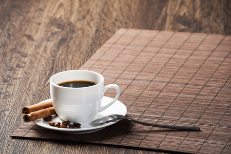 Cup of espresso coffee on wooden table with bamboo mat. Coffee beans and cinnamon sticks on white porcelain saucer. Close up natural aromatic hot drink in restaurant. Morning coffee break. 写真素材