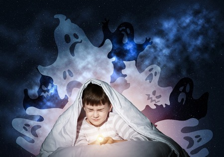 Scared boy hiding under blanket from imaginary spooky monsters. Fearful kid with closed eyes lying in his bed at home. Little boy afraid of nightmares. Covered child in pajamas not sleep at night.