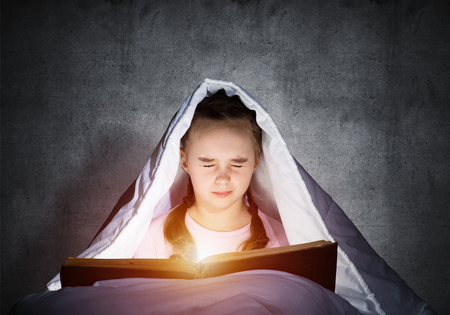 Scared kid with open book and flashlight hiding under blanket. Afraid girl with closed eyes lying in bed at home. Child reading fairy tales. Portrait of girl in pajamas on background of wall.