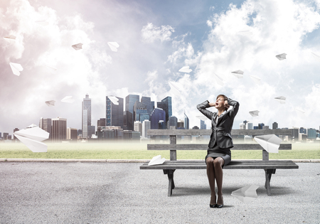 Stressful woman sitting on wooden bench. Emotional screaming girl keeps hands on head. Businesswoman in despair on background modern cityline panorama with flying paper planes. Woman call for help.