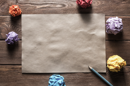 Crumpled brown paper sheet and pencil on wooden table Stock Photo - 123432496