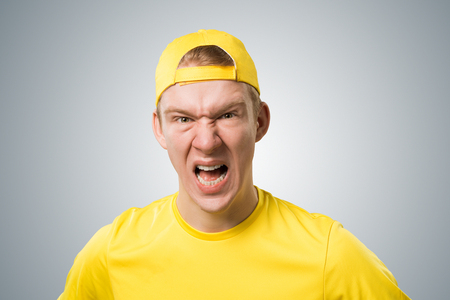 Frenzied teenager screaming with anger. Emotional redhead boy has furious facial expression. Portrait of guy wears yellow t-shirt and baseball cap on grey background. Emotion and expression concept