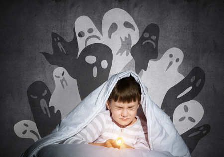 Frightened child with flashlight hiding under blanket. Scared kid with closed eyes lying in bed at home. Little boy in pajamas can not sleep at night. Halloween scary ghostly monsters on wall. Reklamní fotografie - 123464665