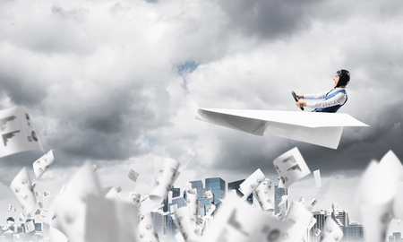 Business accounting and statistics concept with pilot. Aviator driving paper plane above falling paper sheets with infographics. Man flying in paper airplane above paperwork in dramatic cloudy sky. Stok Fotoğraf