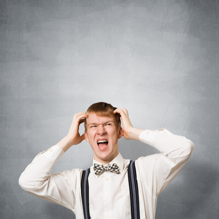 Stressful teenager screaming with panic and keeps hands on head. Emotional redhead boy has irritated facial expression. Guy wears white shirt, bow tie and suspenders on background of grey wall