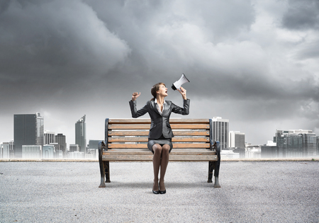 Business woman with megaphone sitting on wooden bench. Female speaker shouting in loudspeaker outdoors. Modern cityline panorama with storm sky. Business marketing and announcement.
